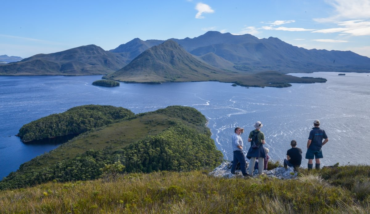 Guide Peter Marmion (L) talking with tourists from the Odalisque on top of Balmoral Hill, Port Davey, Tasmania. The new charter boat will conduct luxury trips in the remote wilderness with a luxury-low impact approach.