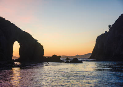 Sunset-through-a-rock-arch-on-the-Breaksea-Islands